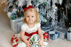 坐在a旁边的一件红色礼服的小女婴迷人的金发碧眼的女人 免版税库存照片