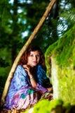 坐在bemoosed岩石旁边的五颜六色的礼服的女孩在森林地国家 免版税库存照片