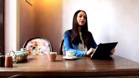 坐在café的女孩,与片剂一起使用 股票录像