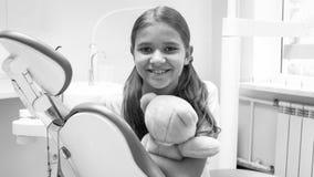 坐在ddentist办公室的愉快的微笑的女孩黑白画象  免版税库存照片
