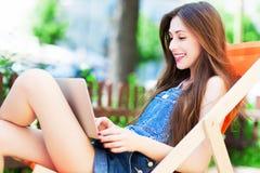 坐在deckchair的女孩使用膝上型计算机 免版税图库摄影