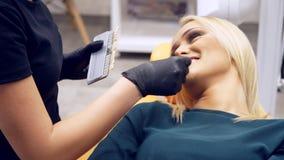 坐在dentistÂ的椅子的一名女性患者,等待辅助的dentistÂ的确定她的牙的树荫颜色 股票视频