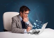 坐在dest和键入在有消息象的膝上型计算机的年轻人 免版税图库摄影