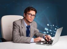坐在dest和键入在有消息象的膝上型计算机的年轻人 库存图片