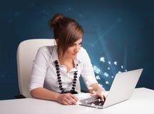 坐在dest和键入在有消息ico的膝上型计算机的小姐 免版税库存图片