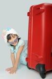 坐在h后的织法帽子和太阳镜的小亚裔女孩 库存照片