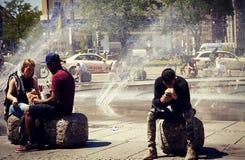 坐在Karlsplatz喷泉的人们在慕尼黑 免版税库存图片