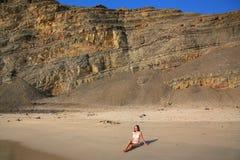坐在La麦纳海滩的比基尼泳装的少妇在Paracas国家 免版税库存图片