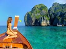 坐在longtail小船前面的少妇在玛雅人海湾的  免版税库存图片