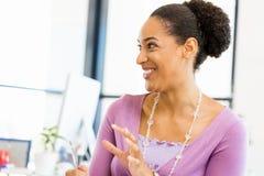 坐在offfice的微笑的美国黑人的办公室工作者画象  库存图片