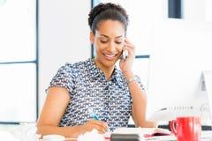 坐在offfice的微笑的美国黑人的办公室工作者画象  免版税库存照片