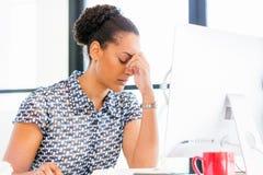 坐在offfice的疲乏的美国黑人的办公室工作者画象  库存图片