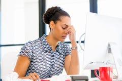 坐在offfice的疲乏的美国黑人的办公室工作者画象  免版税库存照片