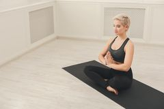 坐在padmasana的少妇实践的瑜伽 库存图片