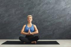 坐在padmasana的少妇实践的瑜伽 免版税库存图片