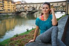 坐在ponte vecchio附近的健身妇女在佛罗伦萨,意大利和 图库摄影
