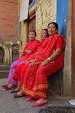坐在Swayambhu寺庙的红色莎丽服的三个尼泊尔夫人 库存照片
