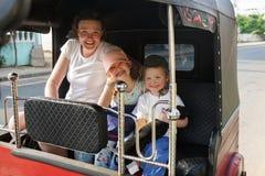 坐在tuk-tuk的家庭在度假,母亲和孩子,获得乐趣 免版税库存照片