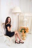 坐在whi前面的一把椅子的一件短的黑礼服的妇女 图库摄影