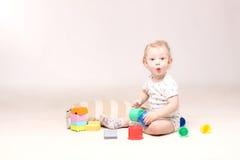 坐地板和使用与他的玩具的惊奇的可爱的男婴 库存照片