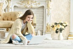 坐地板和使用膝上型计算机的美丽的青少年的女孩 库存图片