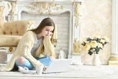 坐地板和使用膝上型计算机的美丽的青少年的女孩 免版税库存照片