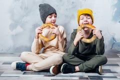 坐地板和愉快地吃百吉卷的两个逗人喜爱的双男孩 免版税库存照片