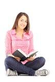坐地板和拿着书的年轻女学生 免版税库存图片