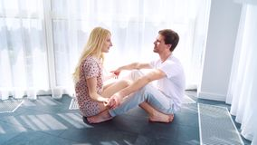 坐地板和握手的年轻爱恋的夫妇的愉快的早晨 股票录像