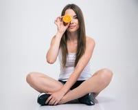 坐地板和盖一只眼睛的女孩用桔子 免版税库存图片