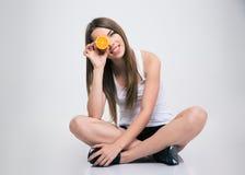坐地板和盖一只眼睛的女孩用桔子 免版税图库摄影