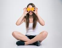 坐地板和盖她的眼睛的女孩用桔子 图库摄影