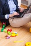 坐地板和键入在膝上型计算机的妇女 免版税图库摄影