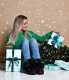 坐地板在冷杉圣诞树附近和作梦关于礼物,礼物和等待的年轻女人奇迹 免版税库存照片