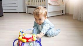 坐地板在卧室和使用与玩具的逗人喜爱的1岁小孩男孩 免版税库存照片