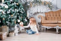 坐地板在圣诞树附近和看在玩具的蓝色牛仔裤的可爱的矮小的白肤金发的女孩 免版税库存照片