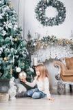 坐地板在圣诞树附近和看在玩具的蓝色牛仔裤的可爱的矮小的白肤金发的女孩 库存照片