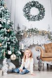 坐地板在圣诞树附近和看在玩具的蓝色牛仔裤的可爱的矮小的白肤金发的女孩 库存图片