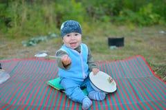 坐地板在营火附近和使用与匙子的小男孩游人,等待,当食物准备好 库存照片