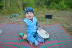坐地板在营火附近和使用与匙子的小男孩游人,等待,当食物准备好 免版税库存照片