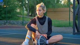 坐地面和使用与球,公园的美丽的白肤金发的女性蓝球运动员在背景中 股票视频