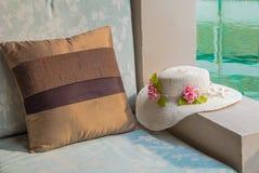 坐垫和帽子在阳台游泳池边 免版税库存图片