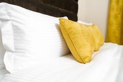 坐垫,在床上的黄色枕头在旅馆客房 免版税库存照片