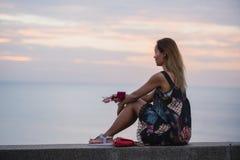 坐堤防和享受看法,在一件短的礼服的美丽的妇女,有手机的 免版税库存图片