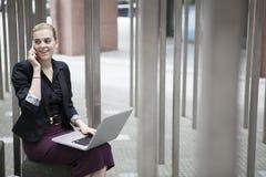 坐外面与膝上型计算机和流动响度单位的年轻女商人 免版税库存图片