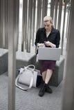 坐外面与膝上型计算机和被装瓶的wat的年轻女商人 免版税库存图片