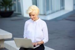 坐外面与膝上型计算机的微笑的少妇 图库摄影