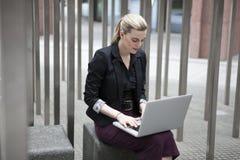坐外面与膝上型计算机的年轻女商人 免版税图库摄影