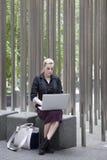 坐外面与膝上型计算机的年轻女商人 免版税库存图片