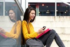坐外面与袋子和手机的微笑的女学生 免版税库存照片